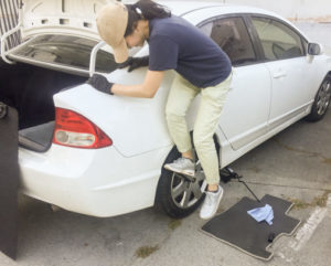 photo of someone standing on a lug nut wrench to remove lug nuts from a wheel